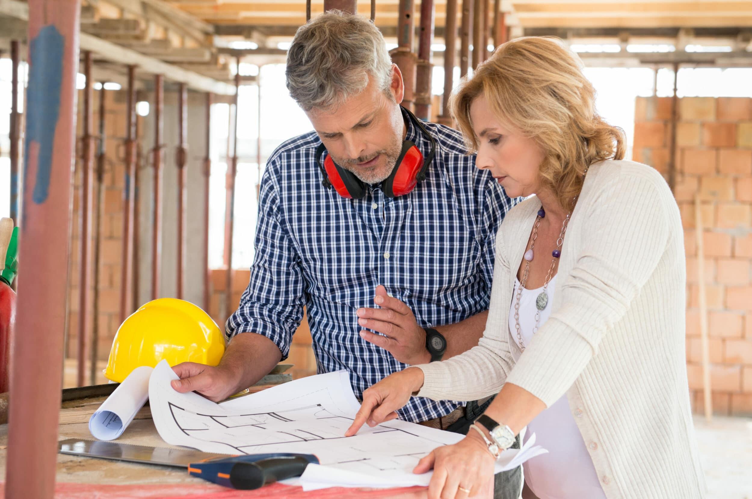 Vrouw overlegt met aannemer over haar nieuwbouw op plan - Chateau Residenties