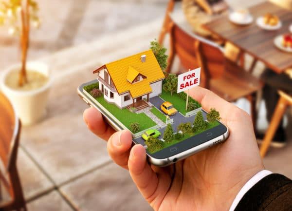 Smartphone met 3D-projectie van huisje symboliseert vastgoed online kopen - Chateau Residenties