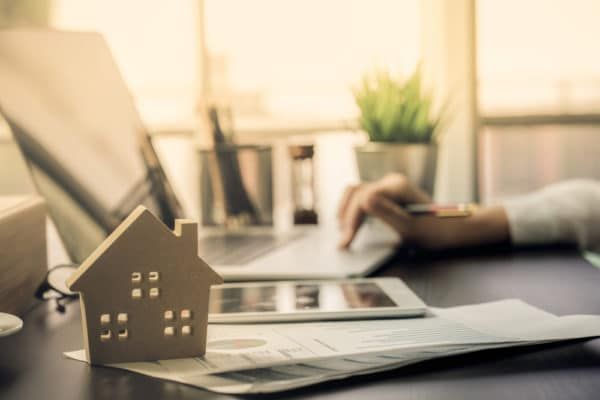 Houten huisje naast laptop symboliseert huis online kopen - Chateau Residenties